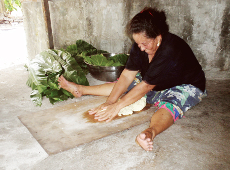 """A woman making a traditional food called """"mar"""" in Pingelap -kneading fermented breadfruit-"""