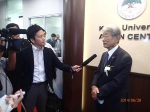 リボン・カット・セレモニーの後、NHKのインタビュー取材に応える松本総長。